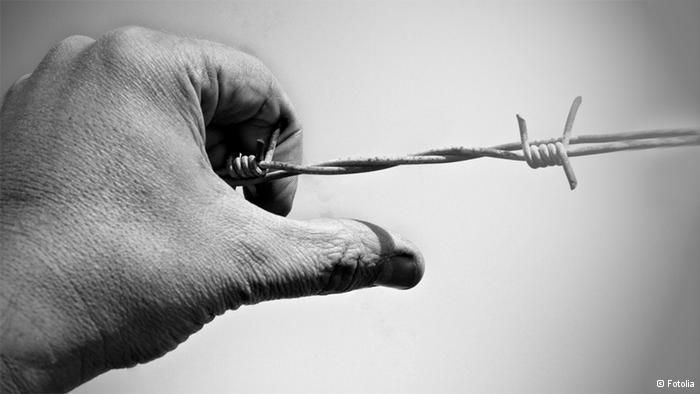 Symbolbild Stacheldraht Hand Gefangenschaft
