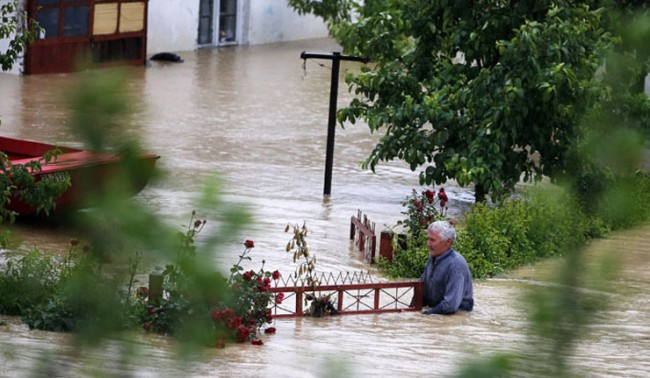 A man stands in his flooded garden in front of his house in the town of Lazarevac, south from Belgrade