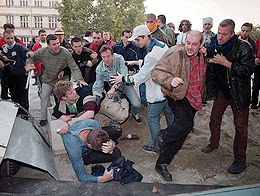 Opposition supporters beat up Dragan Milanovic (on ground - blue shirt), general director of Serbian state television (RTS) in front of the TV building in Belgrade October 5, 2000. Serb state television's three channels went blank and one of its buildings was burning after riot police handed it over to demonstrators. Fires raged inside the Yugoslav parliament building and the television centre on Thursday after thousands of protesters demanded that President Slobodan Milosevic concede electoral defeat. REUTERS/str