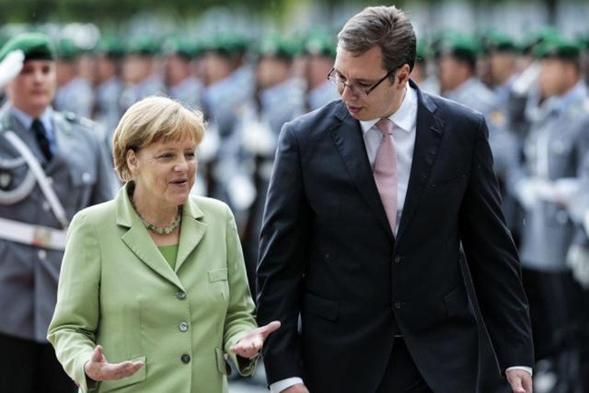 German Chancellor Angela Merkel, left, welcomes the Prime Minister of Serbia Aleksandar Vucic, right, with military honors at the chancellery in Berlin, Wednesday, June 11, 2014. (AP Photo/Markus Schreiber)
