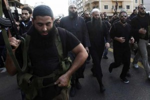 Armed supporters of Lebanon's Sunni Muslim Salafist leader Ahmad al-Assir (front row 3rd R) escort him and Lebanese singer Fadel Shaker (front row 2nd R) during the funeral of two of al-Assir's supporters, who died during Sunday's fighting with supporters of Lebanon's Hezbollah, in Sidon, southern Lebanon November 12, 2012. Three people were killed on Sunday when fighting broke out in the Lebanese coastal city of Sidon between followers of al-Assir and supporters of the Lebanese Shi'ite guerrilla movement Hezbollah, a security official said. REUTERS/Ali Hashisho (LEBANON - Tags: CIVIL UNREST POLITICS ENTERTAINMENT) - RTR3ABCC