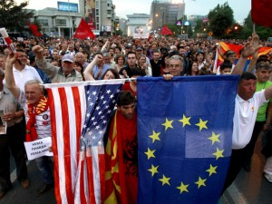 "A protestor holds the flags of the United States, left, and the European Union, right, while others chant ""No justice, no peace"" during a march in front of the parliament building in Skopje, Macedonia, Monday, April 18, 2016. Macedonia has entered in a second week protests with thousands marching peacefully late on Monday in downtown of the capital Skopje after the country's president pardoned dozens of politicians who were facing criminal proceedings for alleged involvement in a wiretapping scandal. (AP Photo/Boris Grdanoski)"