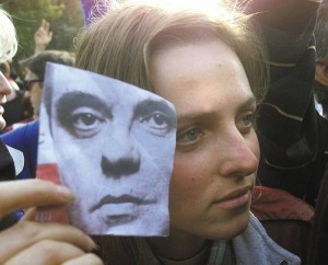 An opposition demonstrator holds up a picture of Democratic Opposition of Serbia Presidential candidate Vojislav Kostunica in front of the federal parliament building during rally in Belgrade, Yugoslavia Friday, Oct. 6, 2000. Tens of thousands gathered outside the parliament, and aides to opposition leader Vojislav Kostunica said he would be inaugurated as the new president once parliament can reconvene, possibly this weekend. (AP Photo/Dusan Vranic)